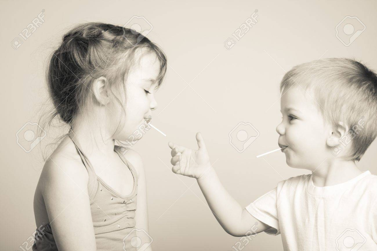 black and white photo of siblings playing with each others lollipops - 37346491