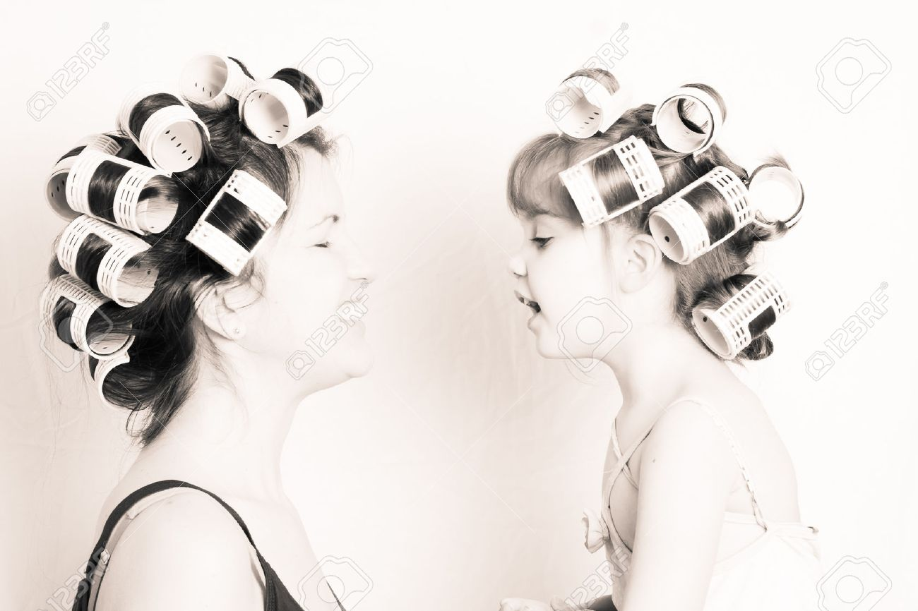 mother and daughter with rollers in their hair having fund together - 37346844