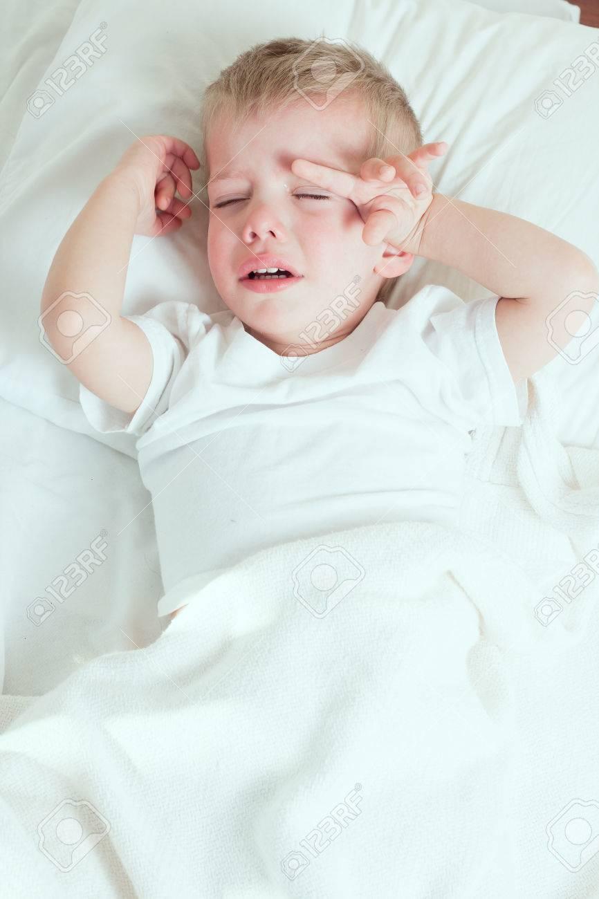 sick toddler boy wearing white tshirt crying in bed - 37477917