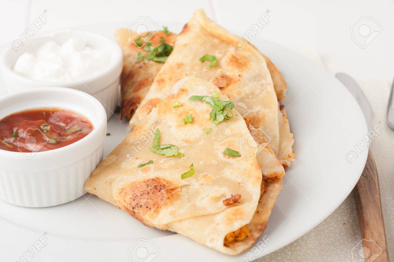 original mexican quesadilla garnished with cilantro on white plate with sour cream and salsa - 37708218