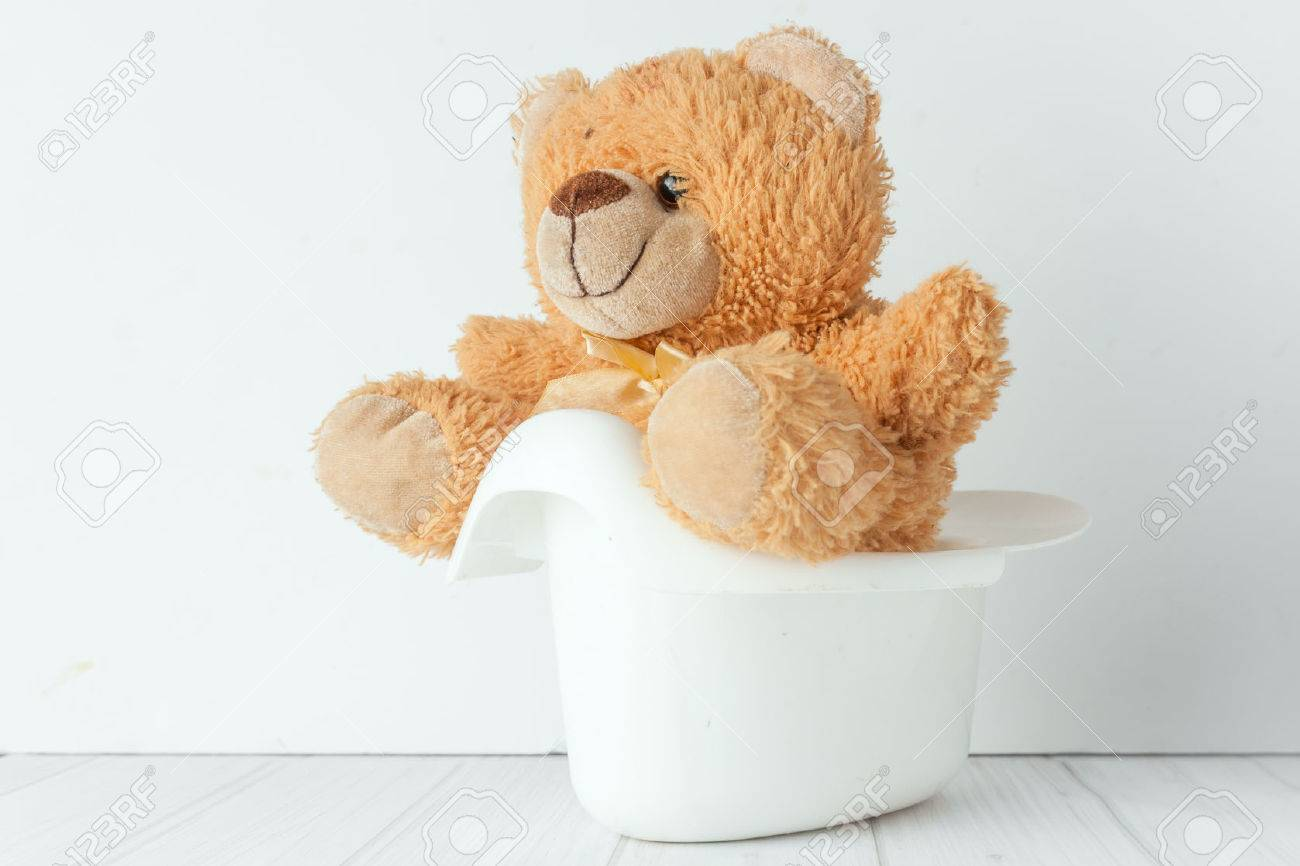 A teddy bear in a white potty next to stack of diapers. Conceptual image representing potty training - 38496941