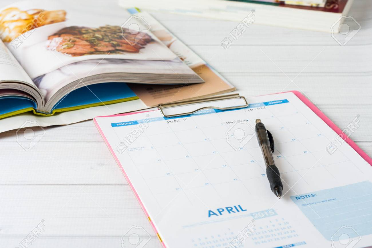 Monthly calendar and stack of cookbooks. Conceptual image showing meal planning in progress. Shallow depth of field - 38574514