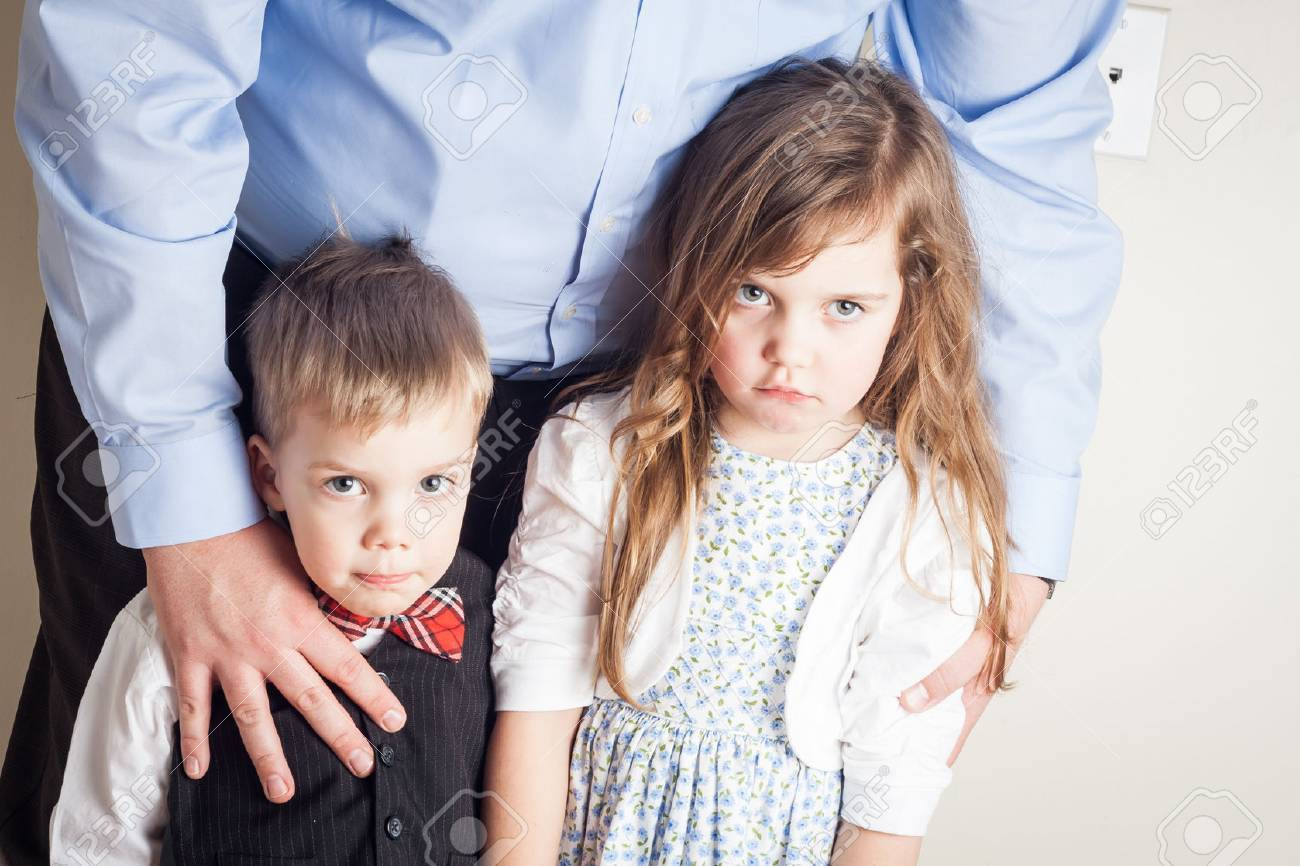 brother and sister held by their father, with guilt on their faces, great parenting image - 39983256