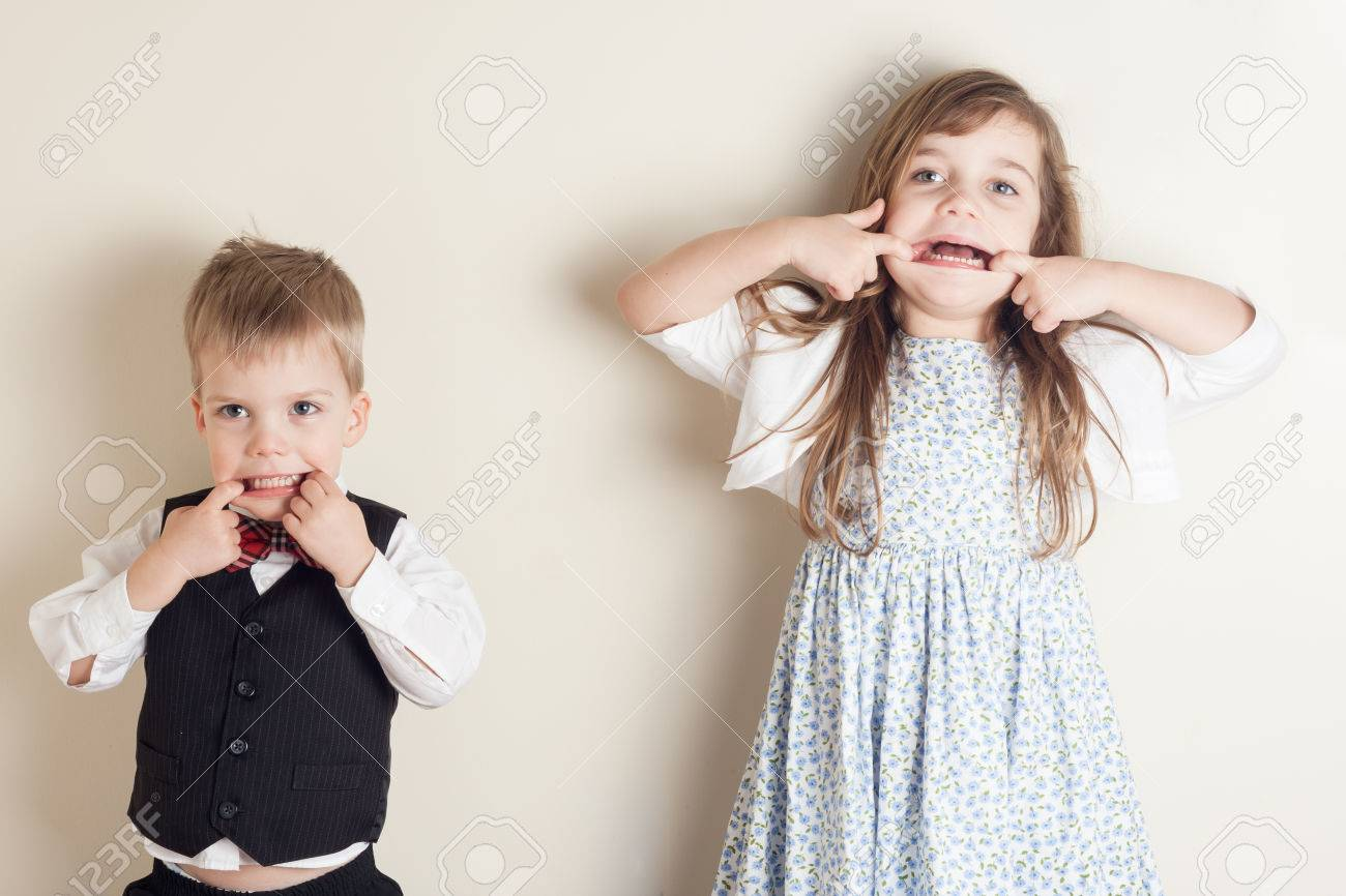 brother and sister standing against a wall and making faces - 39983257