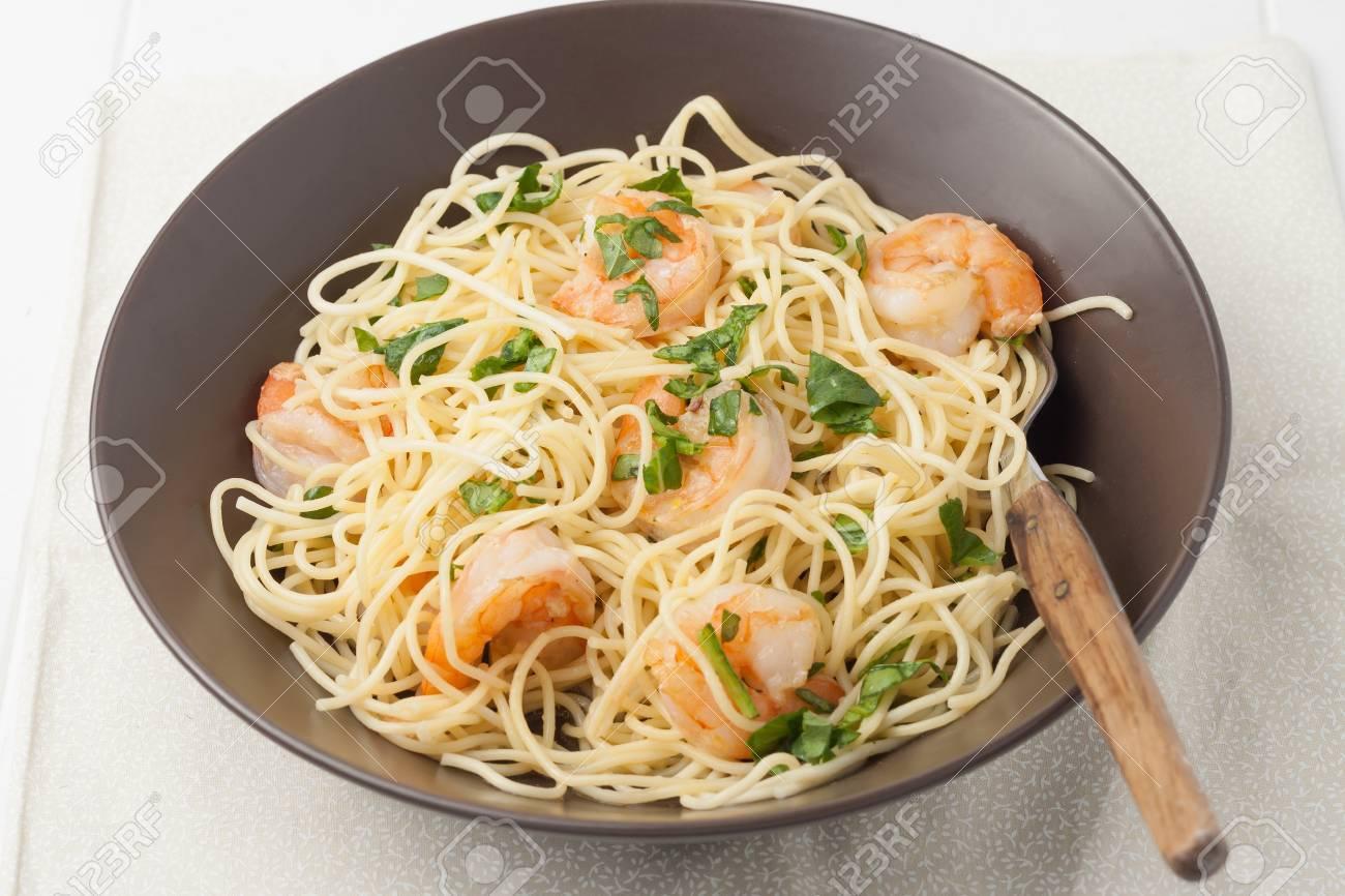 close up of a brown bowl of shrimp scampi - 38497850
