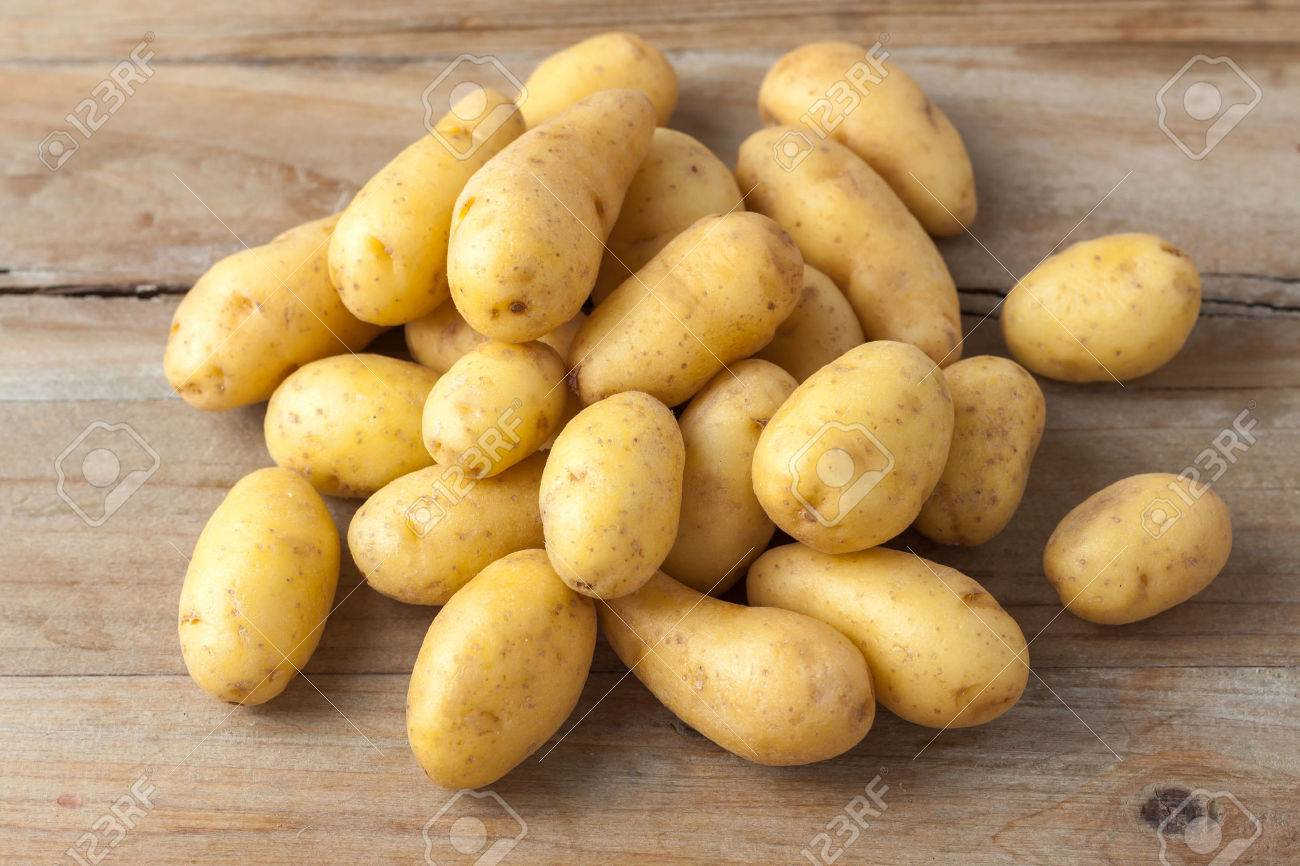 raw baby potatos on rustic wooden background - 38976365