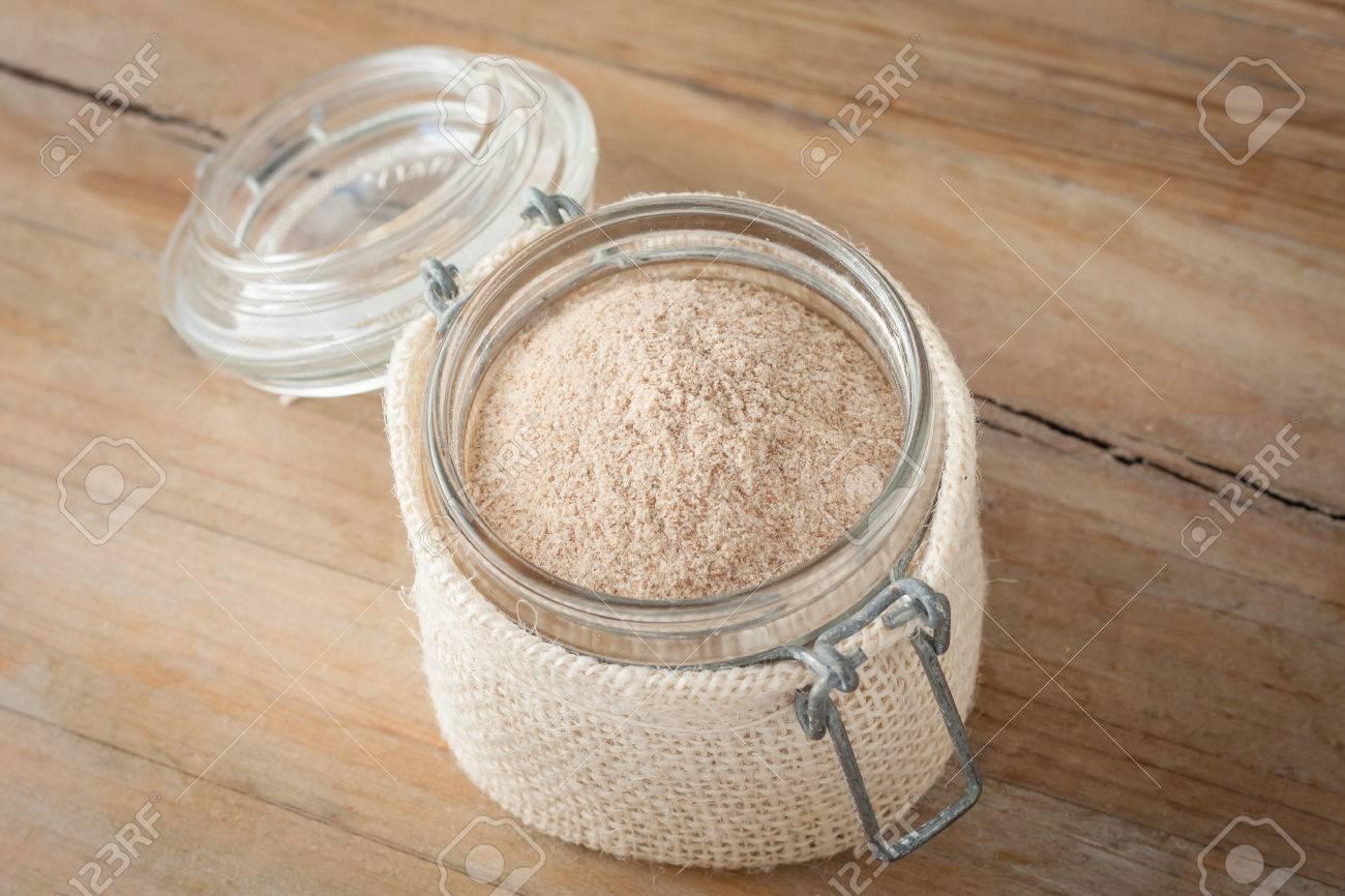 psyllium husks powder in glass jar over wooden rustic background - 39047076