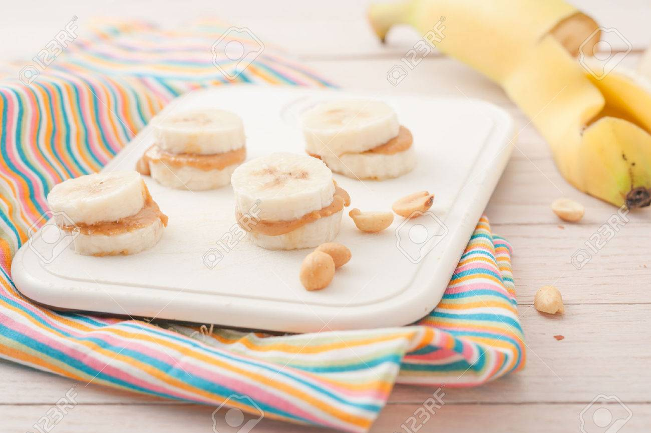banana slices with peanut butter on white chopping board - 43932731