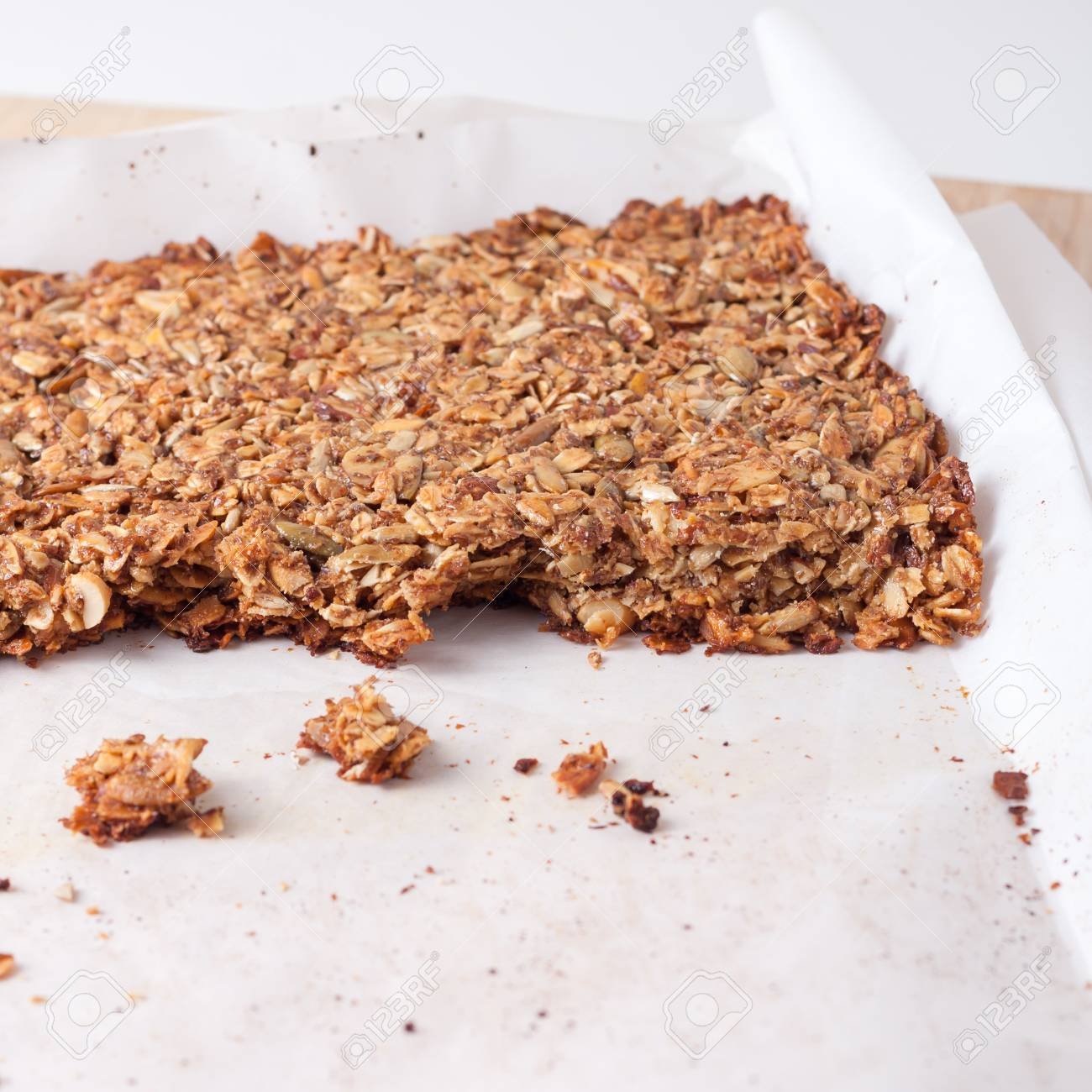 fresh home made granola bars made with coconut oil, nuts and seeds on a baking sheet, isolated - 44167900