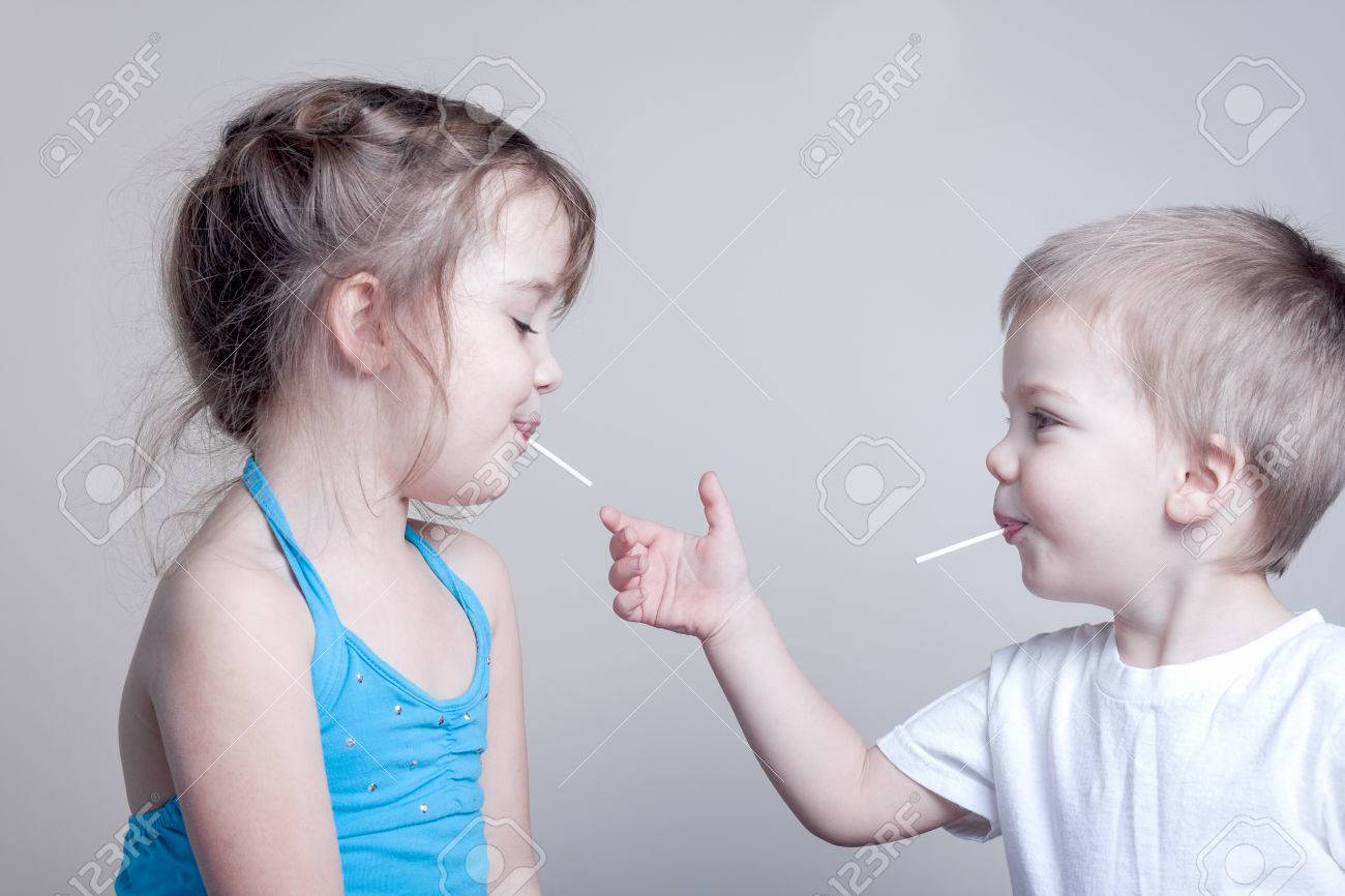 siblings having fun with lollypops - little brother is trying to grab his sister's lollypop, horizontal image - 45837920