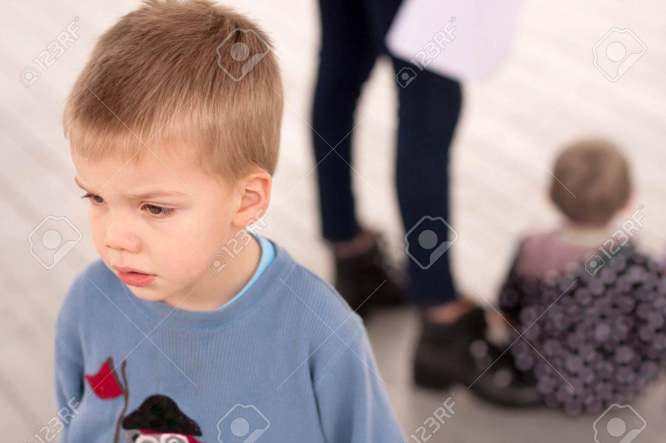 sad blond boy jealous about being neglected by his mother or caregiver who is giving attention to another child - 47052453