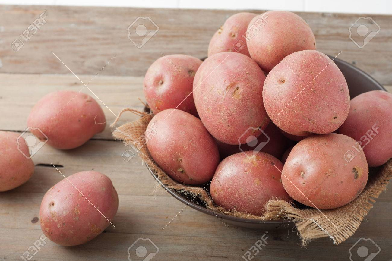 large red potatoes in a bowl on wooden background - 47052460