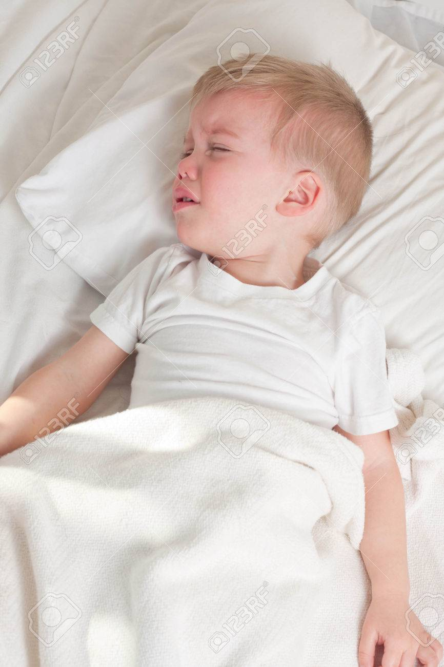 a sick blond toddler wearing white t-shirt lying in bed and crying - 47320499