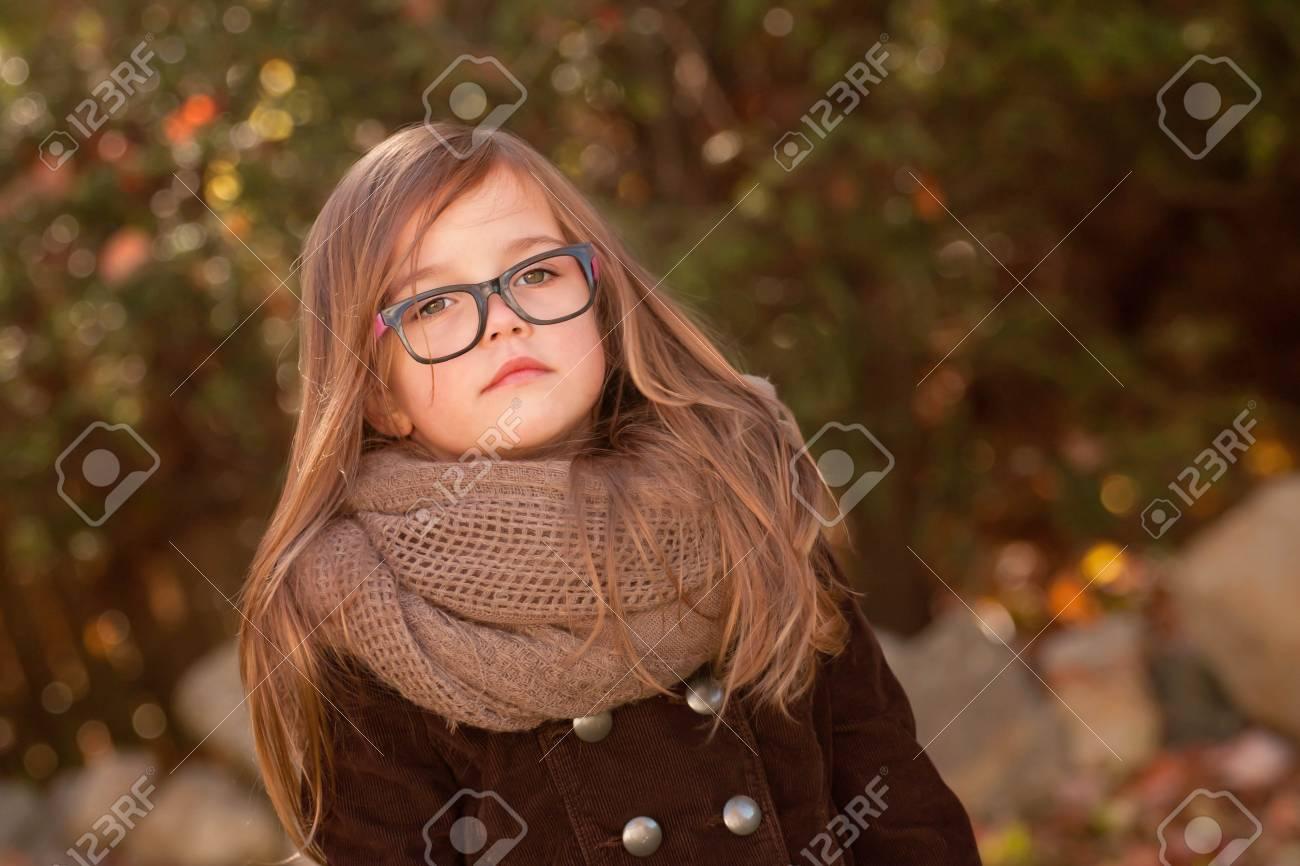 Banque d images - Petite fille aux longs cheveux bruns portant de grosses  lunettes noires debout à l extérieur sur une journée d automne frisquet 4fbb64c06e22