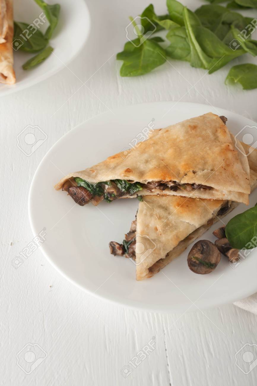 mushroom spinach quesadilla on white plate, selective focus - 48627400