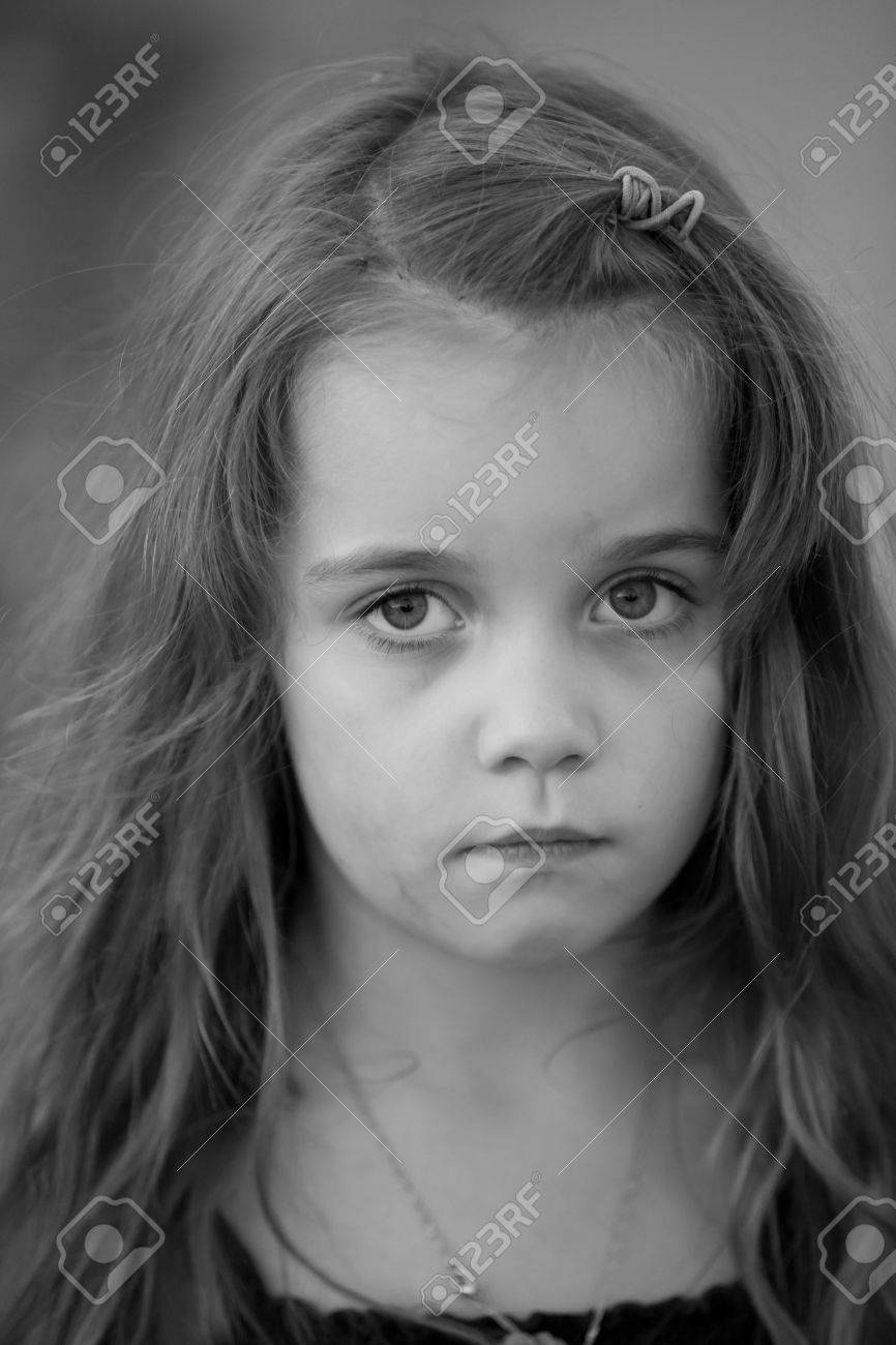 Artistic low key black and white portrait of a sad little girl