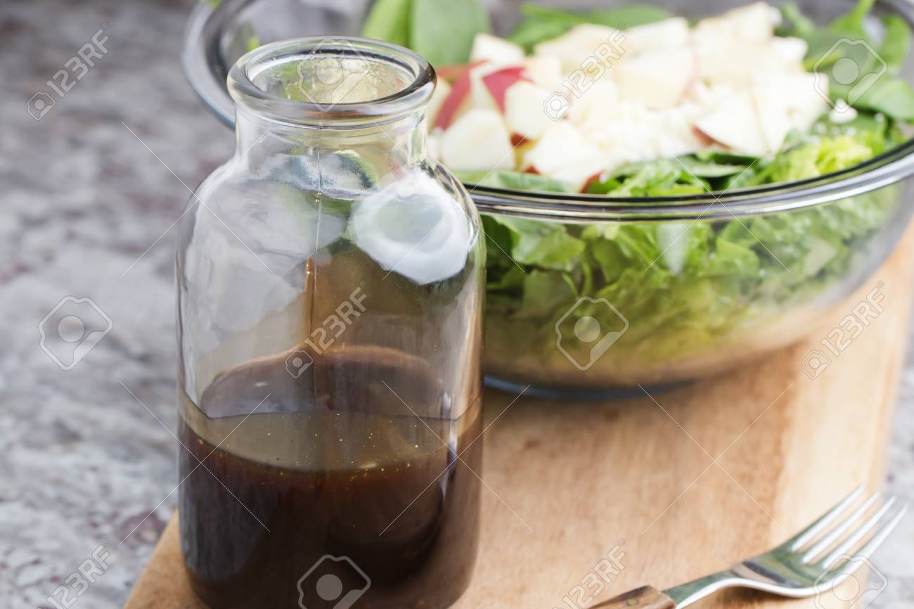 a glass bottle with salad dressing consisting of balsamic vinegar, honey and olive oil and spices - 71241292