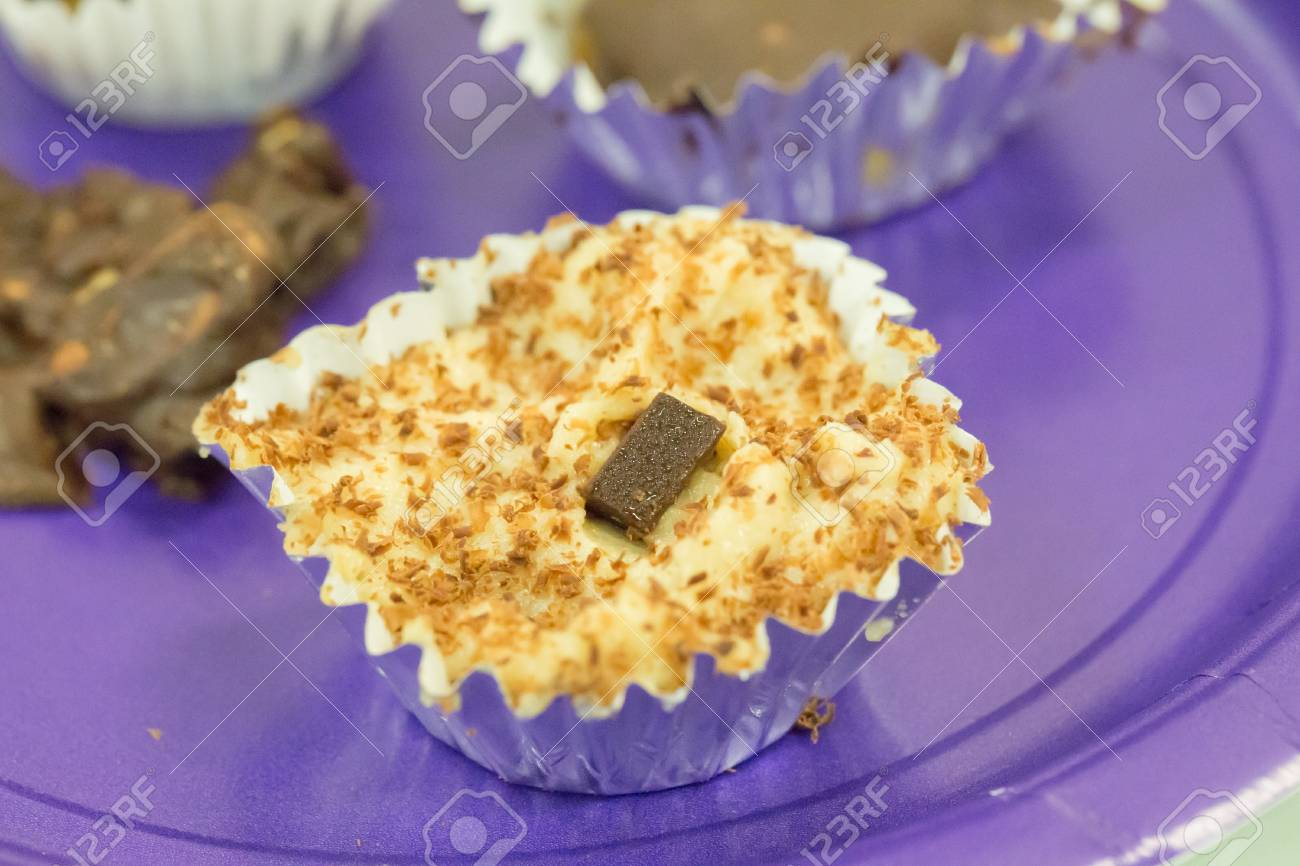 mini vegan cheescake made with cashews in silver wrapping with chocolate topping on purple plate - 120352038