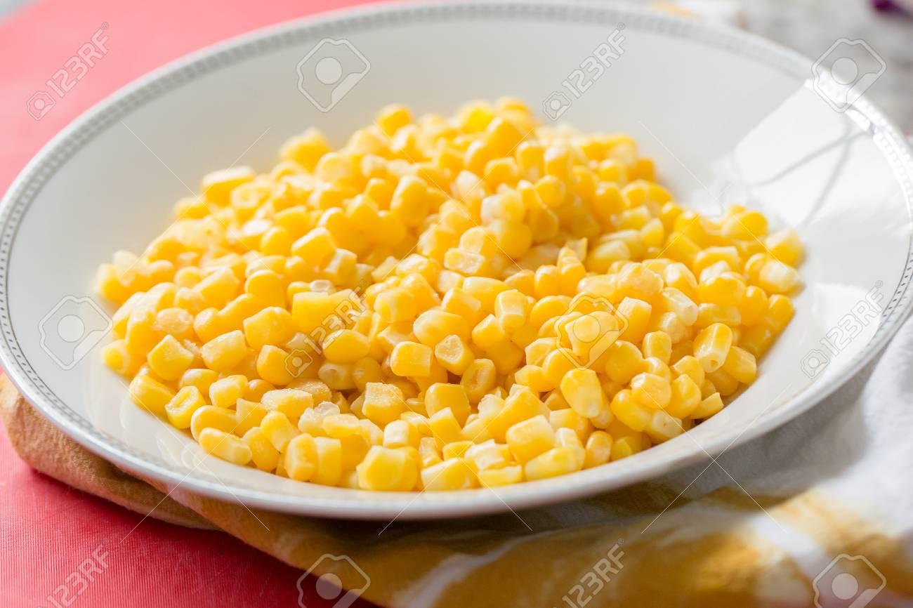 fresh sweet yellow corn kernels in white bowl - 120352041