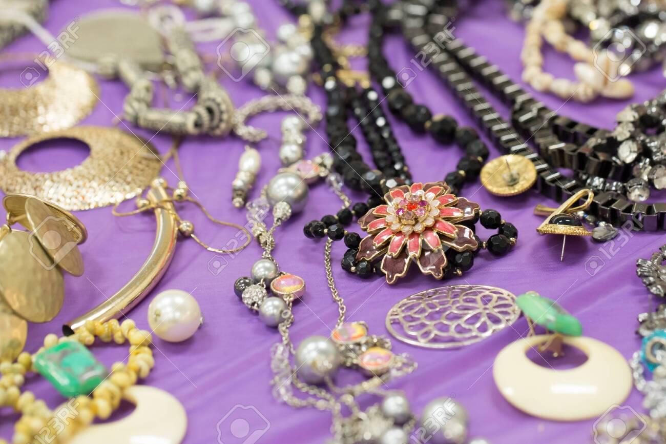variety of homemade jewellery on purple table - 120352051