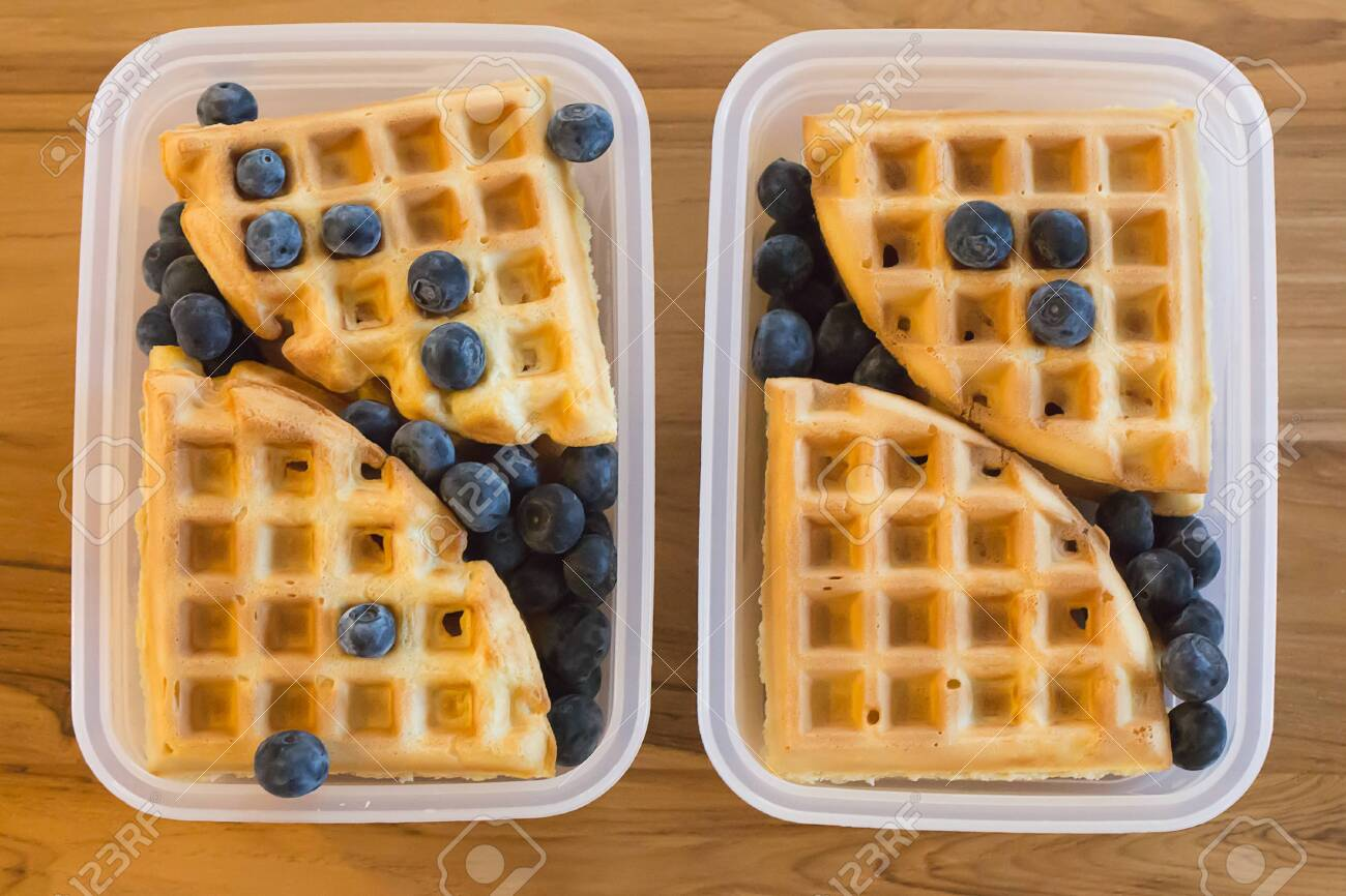 school lunch for kids: plain waffles and berries in a plastic container, two portions - 120352070