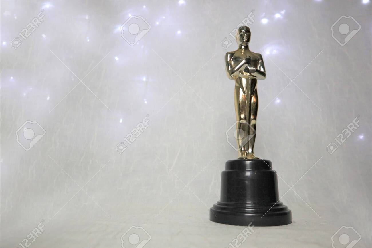 The golden statue of Oscar on a white background, with illumination around a prestigious figure. Success and victory concept - 132029820