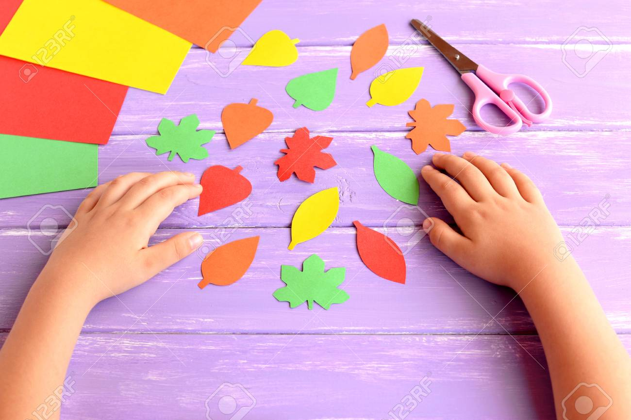 Child cut out of colored paper fall leaves  Kid doing fall paper