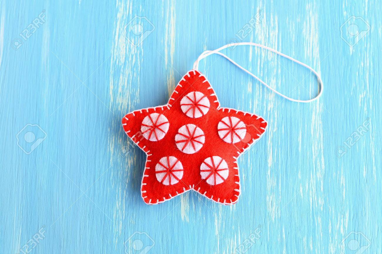 Red christmas star ornament isolated on a blue wooden background