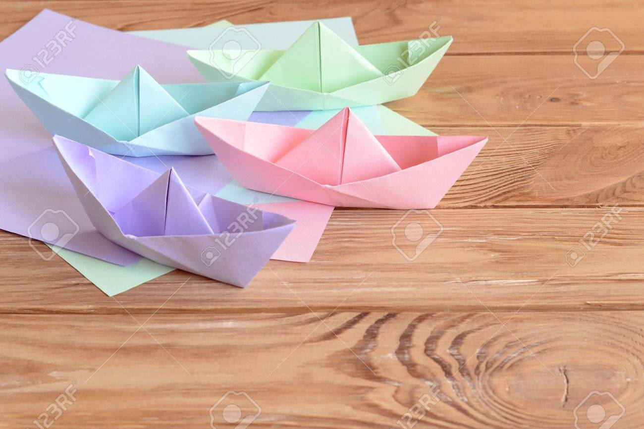 Pink Green Blue Lilac Paper Boats Toys On Wooden Background Sheets Of