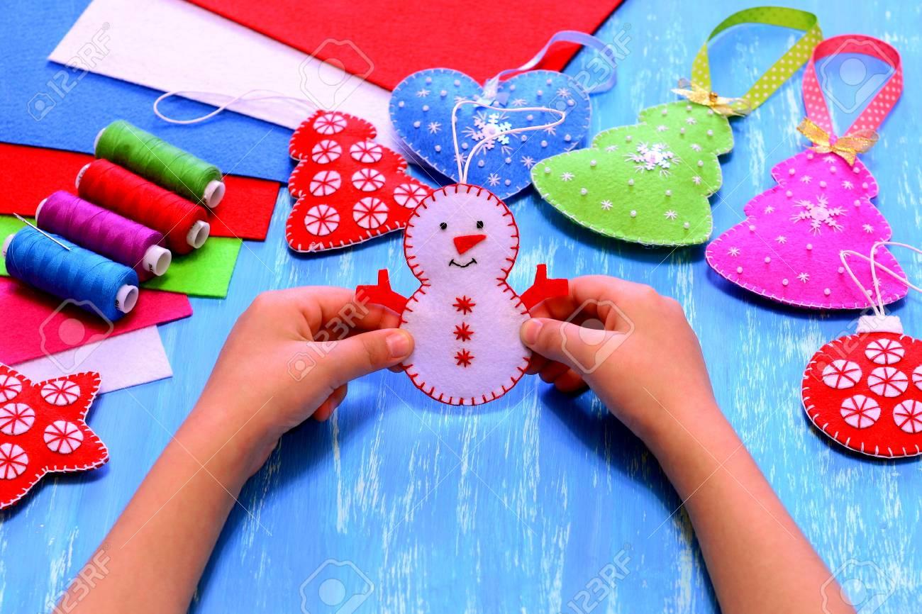 Kind Hält Eine Filz Schneemann Ornament In Seinen Händen. Nähendes ...