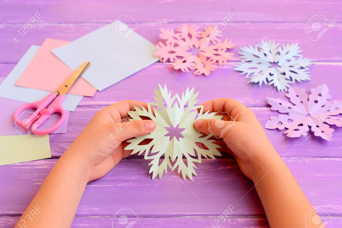 Child holds a paper snowflake in hands child shows snowflake child holds a paper snowflake in hands child shows snowflake decoration colored paper jeuxipadfo Image collections