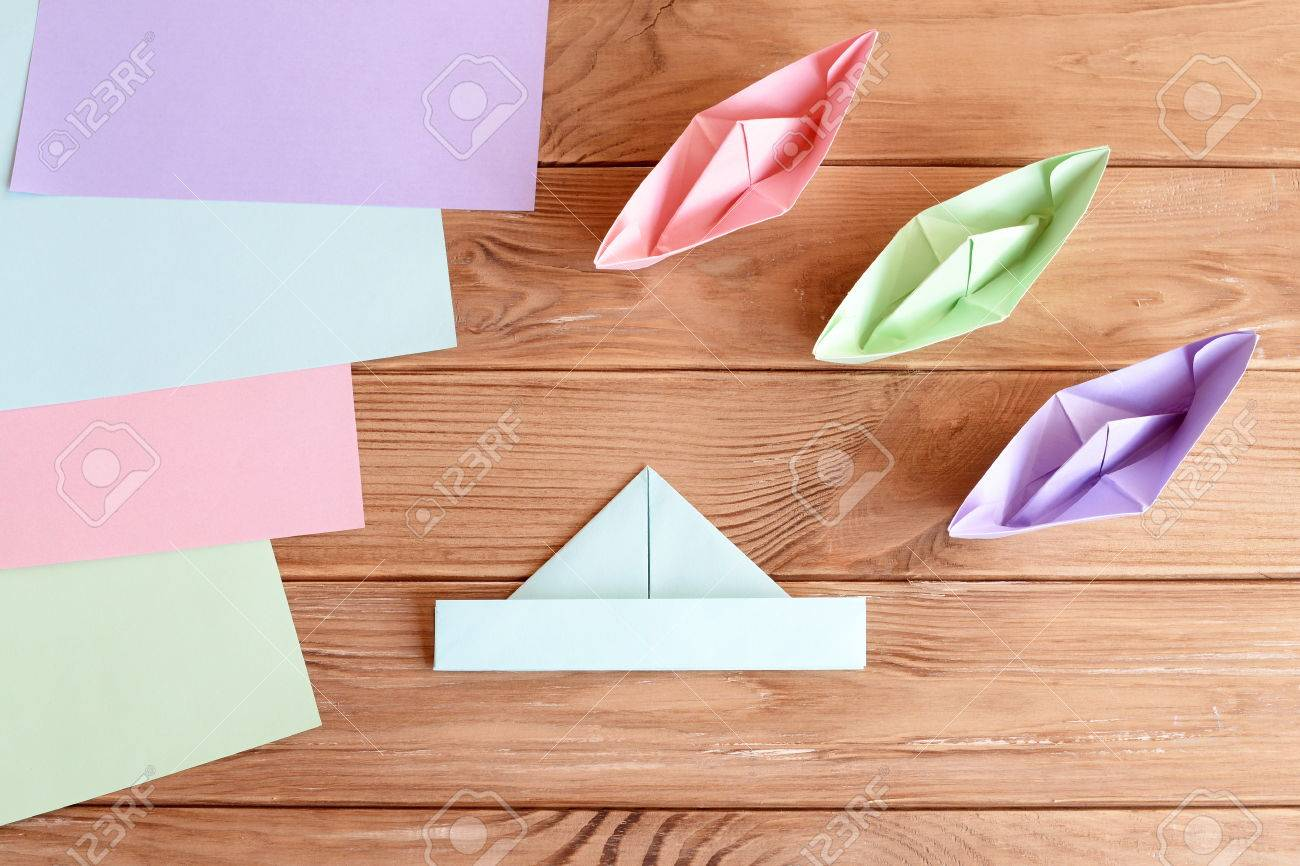 Set of origami boats and square sheets of colored paper on a set of origami boats and square sheets of colored paper on a wooden table how jeuxipadfo Image collections