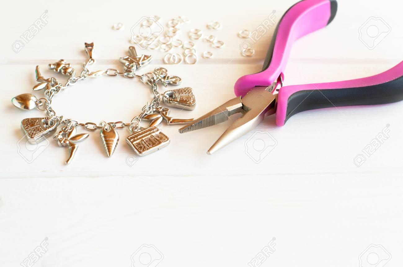 pinces, bracelet, bague en métal sur un fond en bois blanc. comment