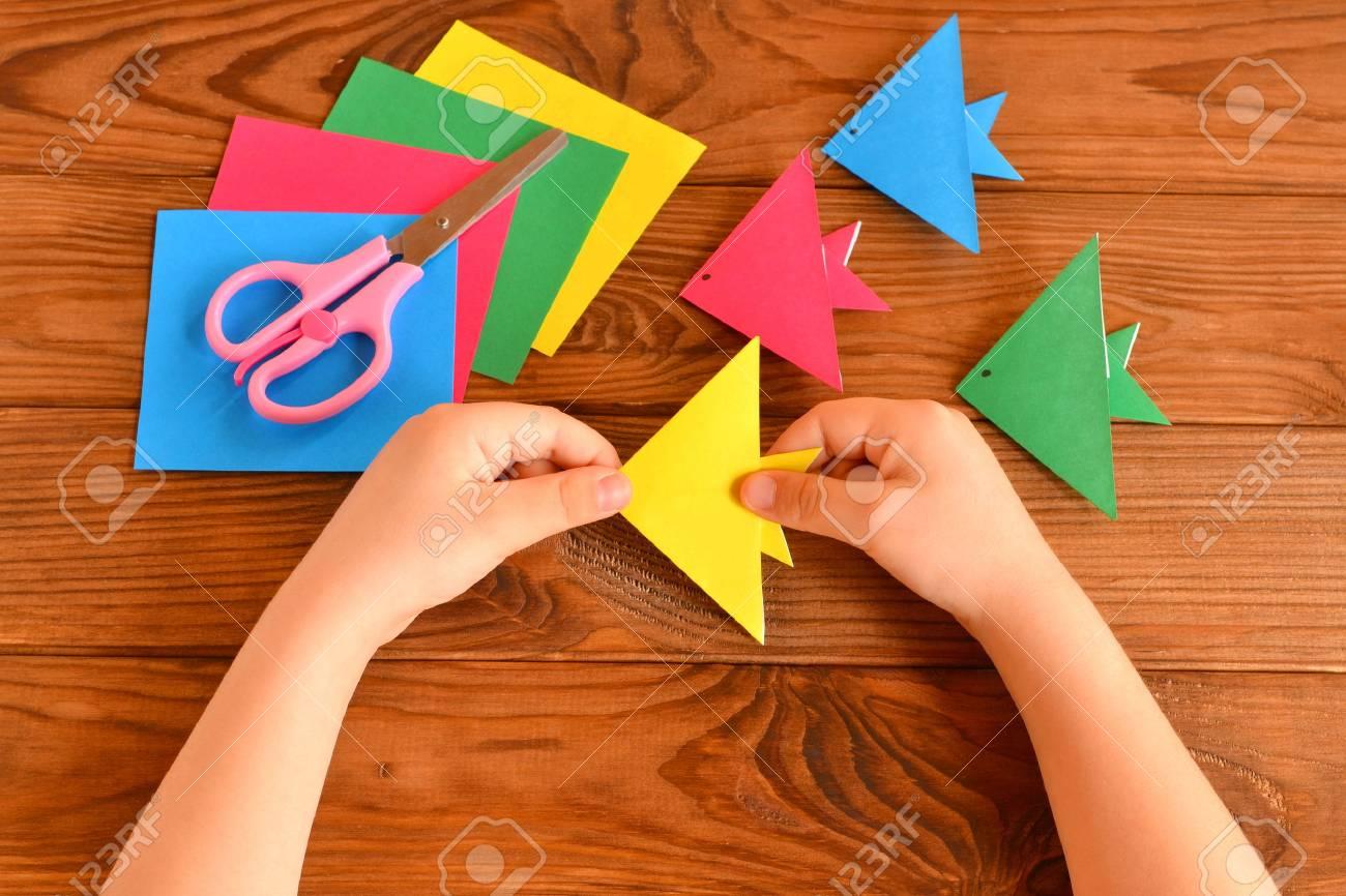 Origami Coloridos Peces, Hojas De Papel. El Niño Sostiene Un Pez ...