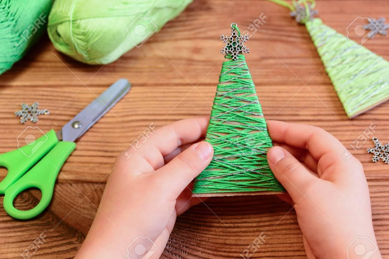 Decorazioni In Legno Per Albero Di Natale : Bambino è in possesso di una decorazione albero di natale nelle sue