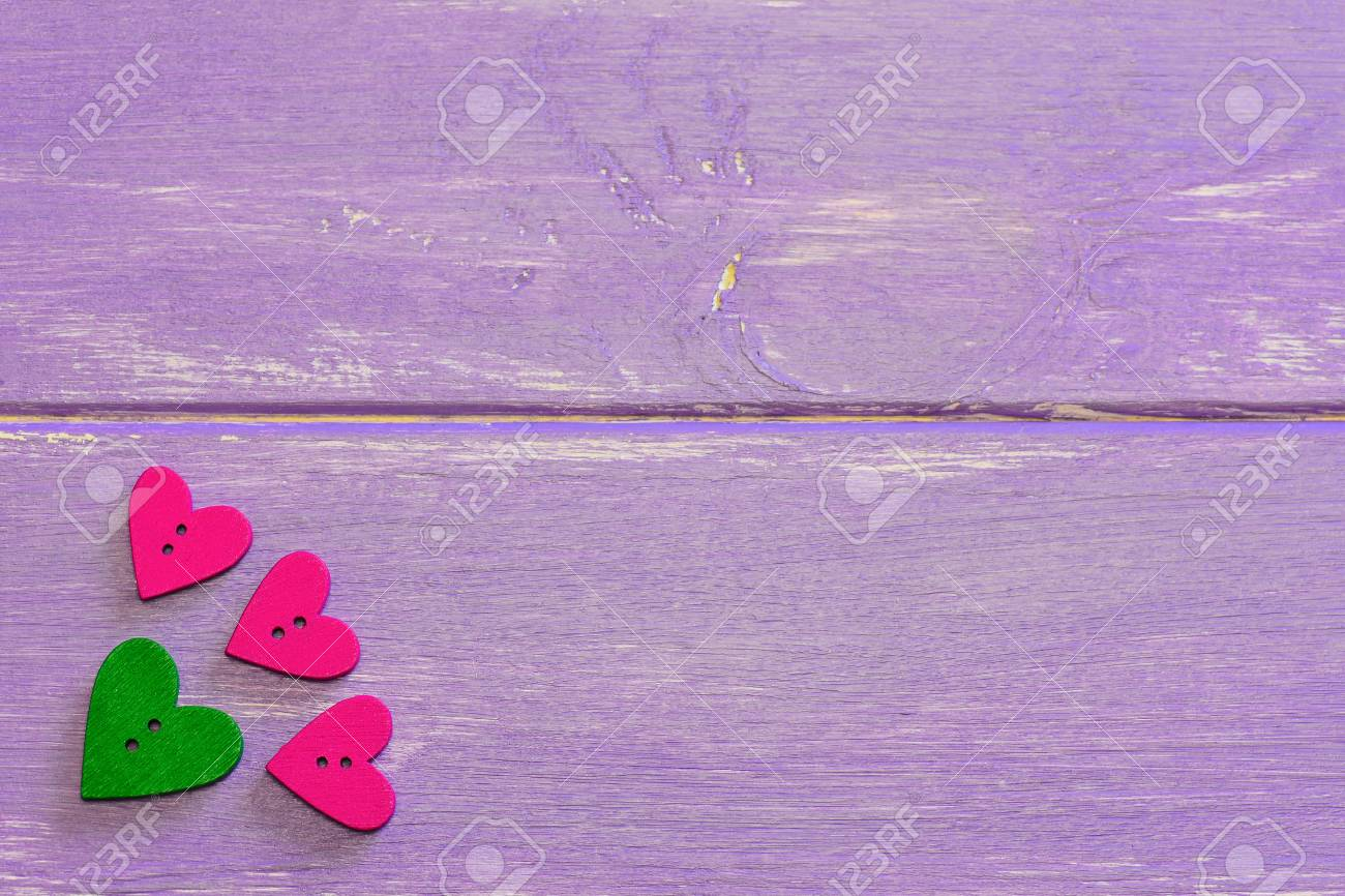 Heart shaped buttons  Wooden buttons on a purple wooden background