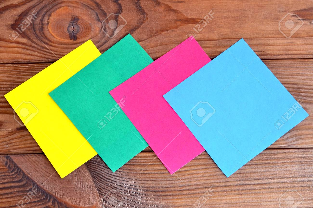 multicolored paper square sheets on a wooden table paper set