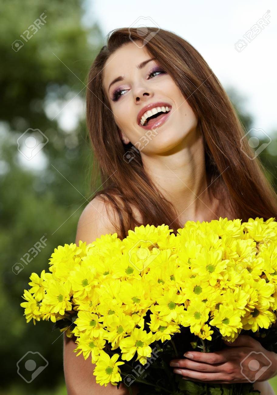 Young woman holding yellow flowers Stock Photo - 9867821