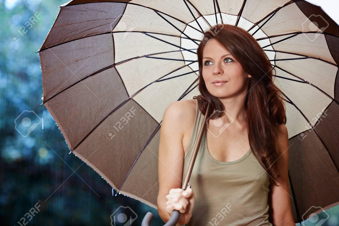 13abb1b5b60 Beautiful woman holding umbrella out in the rain Stock Photo - 10074328
