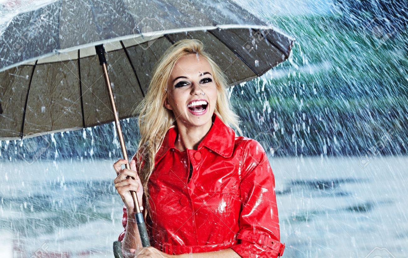 d67265466 Woman In Raincoat Smiling As She Holds Umbrella Stock Photo, Picture ...