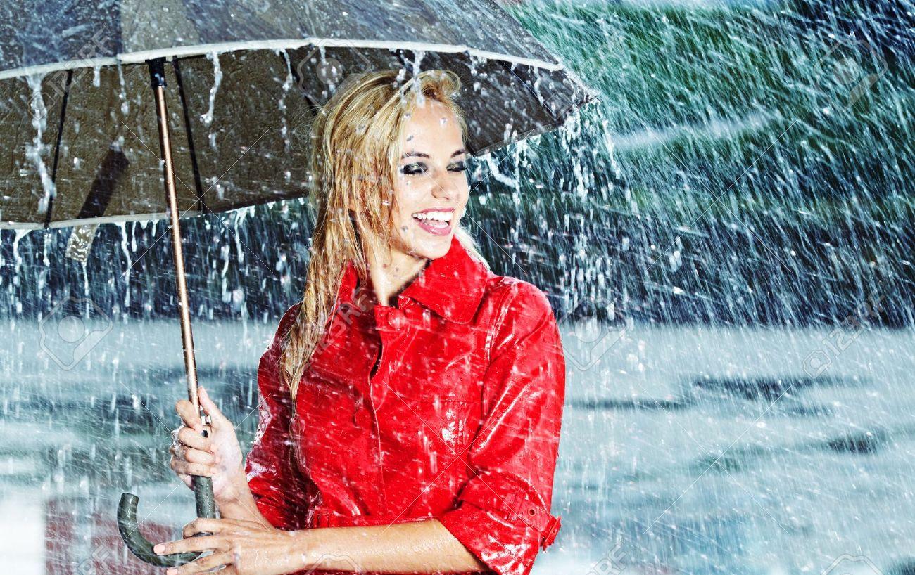 4ba868c4e48 Beautiful blonde woman holding umbrella out in the rain Stock Photo -  14635579