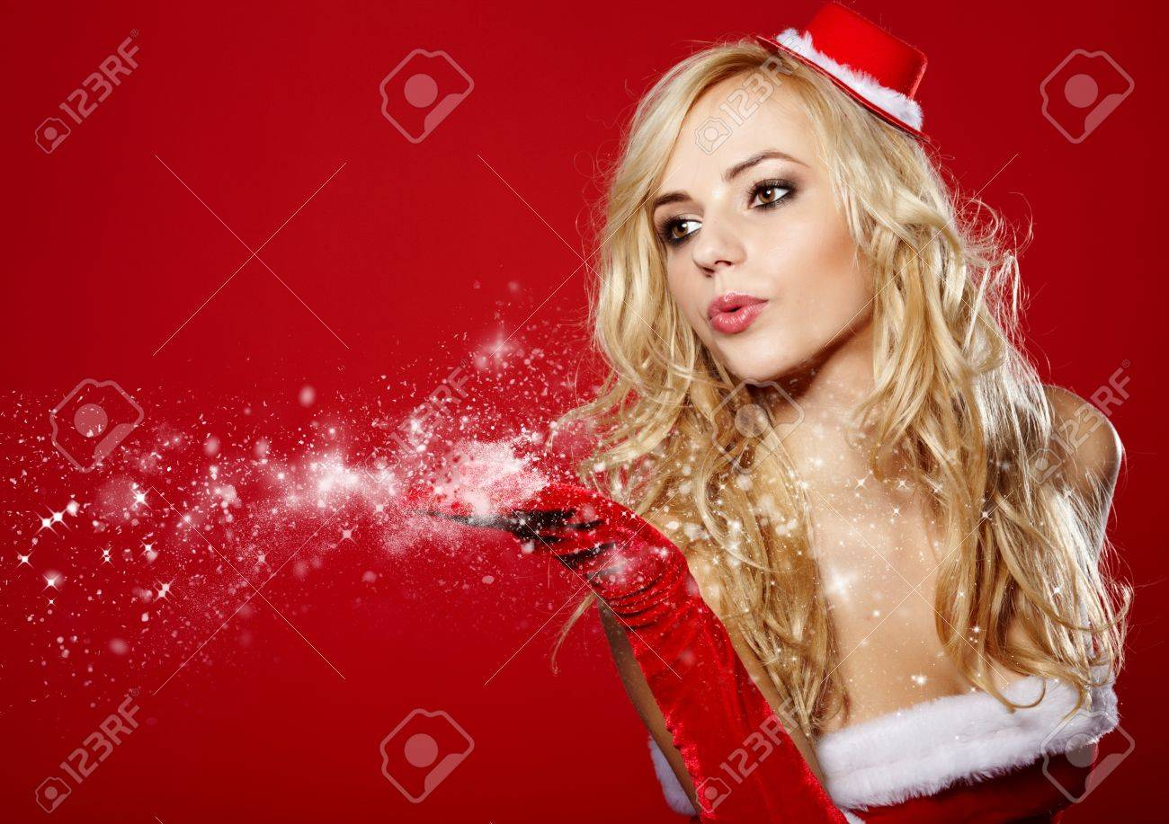 pretty young brunette woman dressed as Santa blowing on the snow on her hands Stock Photo - 16166122