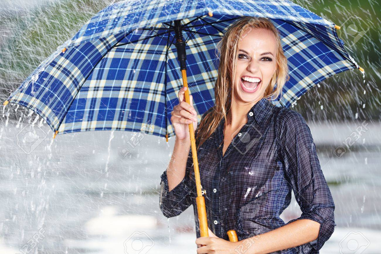 fd6ce575f62 Beautiful blonde woman holding umbrella out in the spring rain Stock Photo  - 18213195