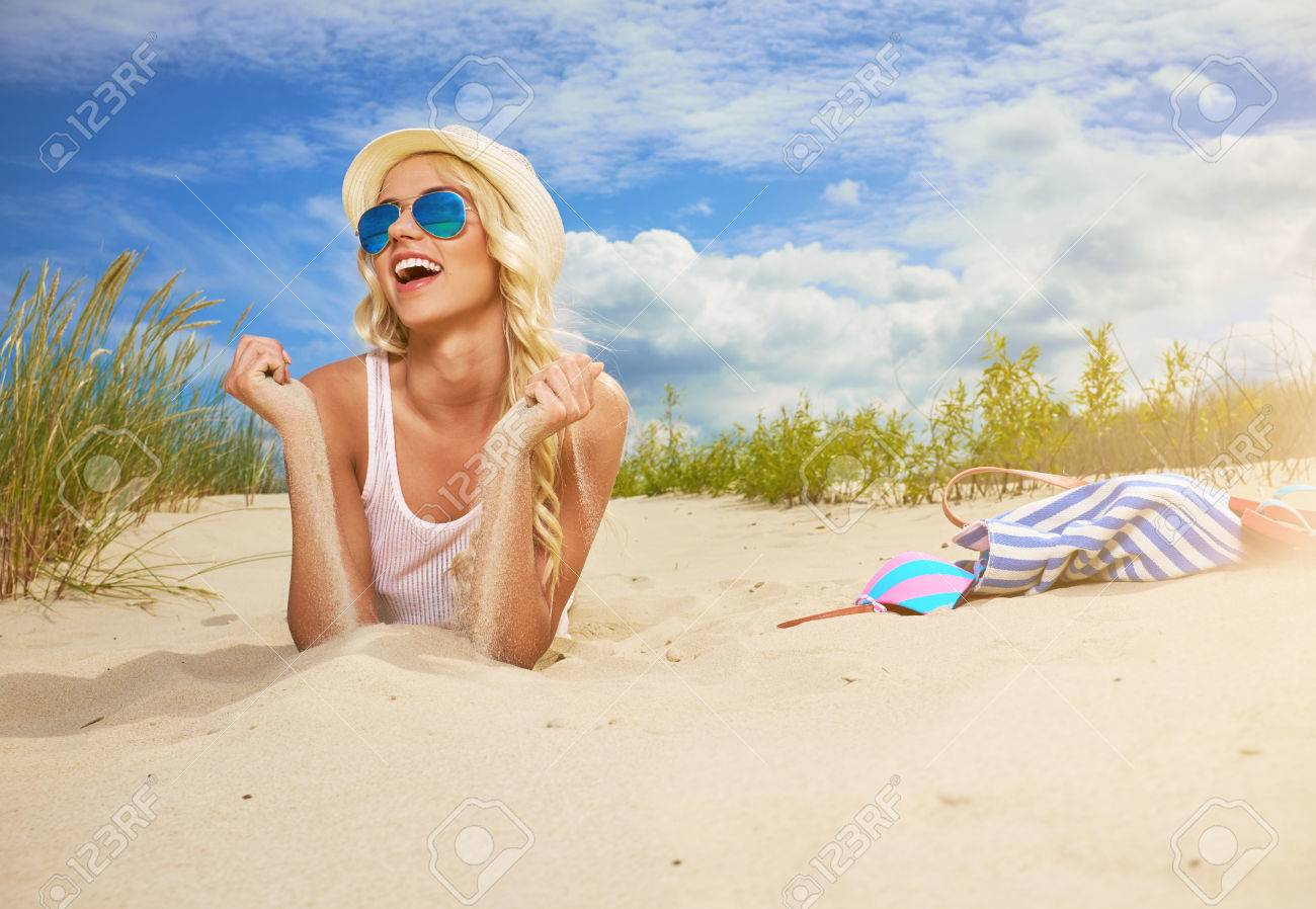 57b67a10905 Beach woman funky happy and colorful wearing sunglasses and beach hat  having summer fun during travel