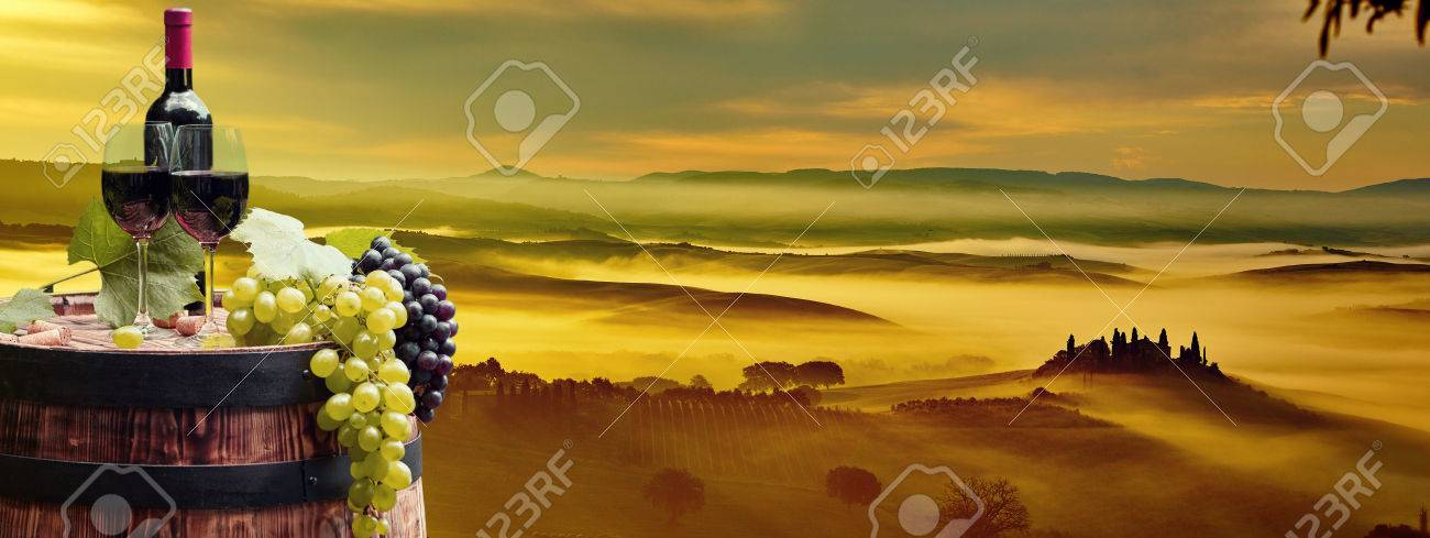Red wine bottle and wine glass on wodden barrel. Beautiful Tuscany background - 46624100