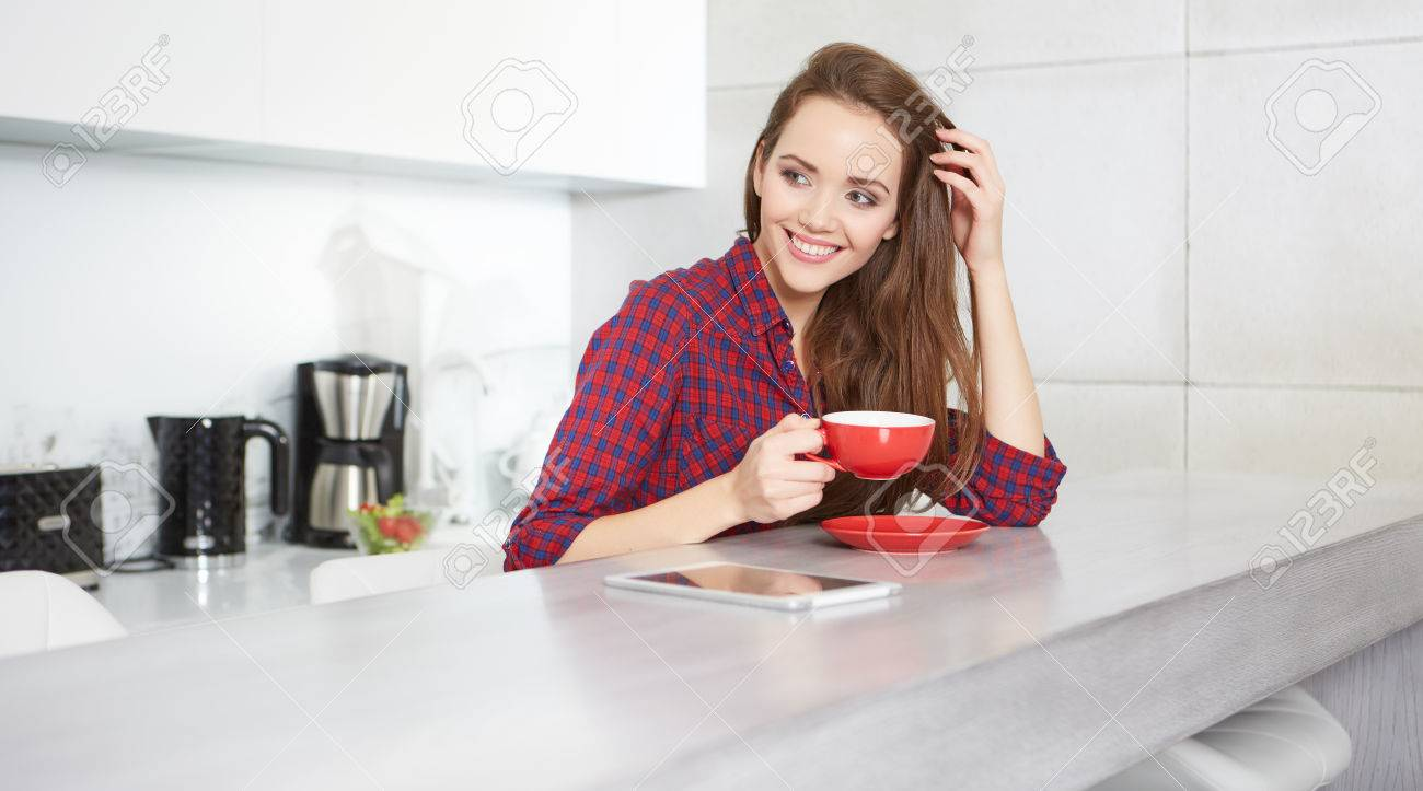 young woman drinking coffee at home in the morning - 50876274