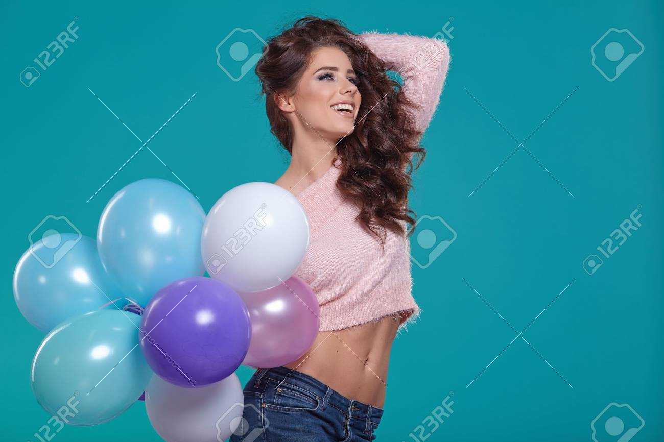 Young pretty woman with colored balloons, turquoise background - 51590633