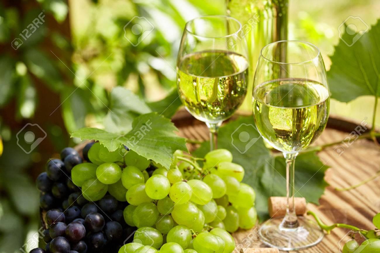 Grape and white wine on wooden barrel on garden terrace - 51904294