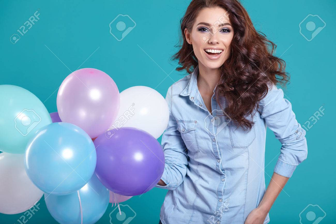Happy young woman standing over blue wall and holding balloons. Pleasure. Dreams. Toned. - 51924426