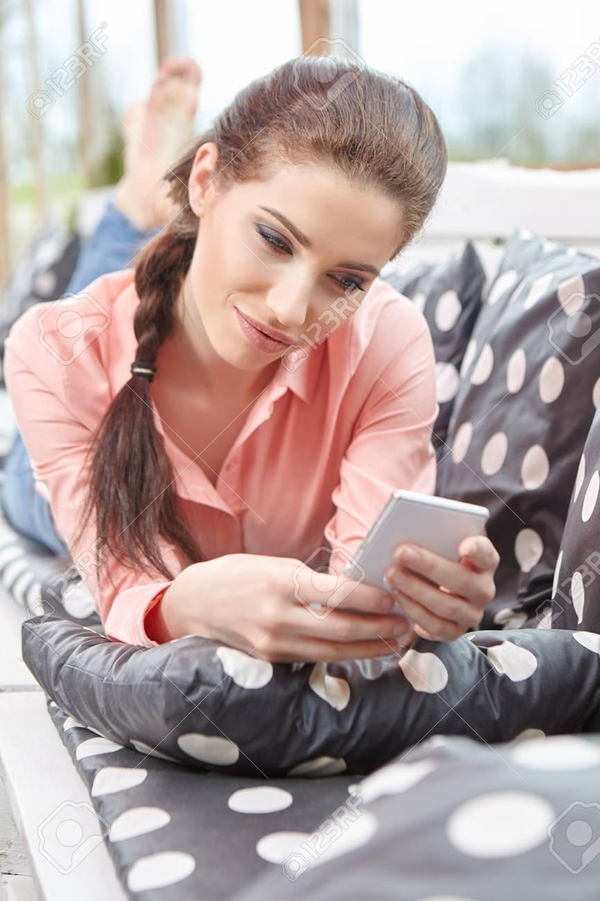 Mujer Joven Que Habla Con El Teléfono Móvil En La Terraza De Su Casa